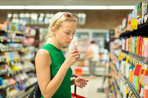 femme qui sent un savon dans un supermarché