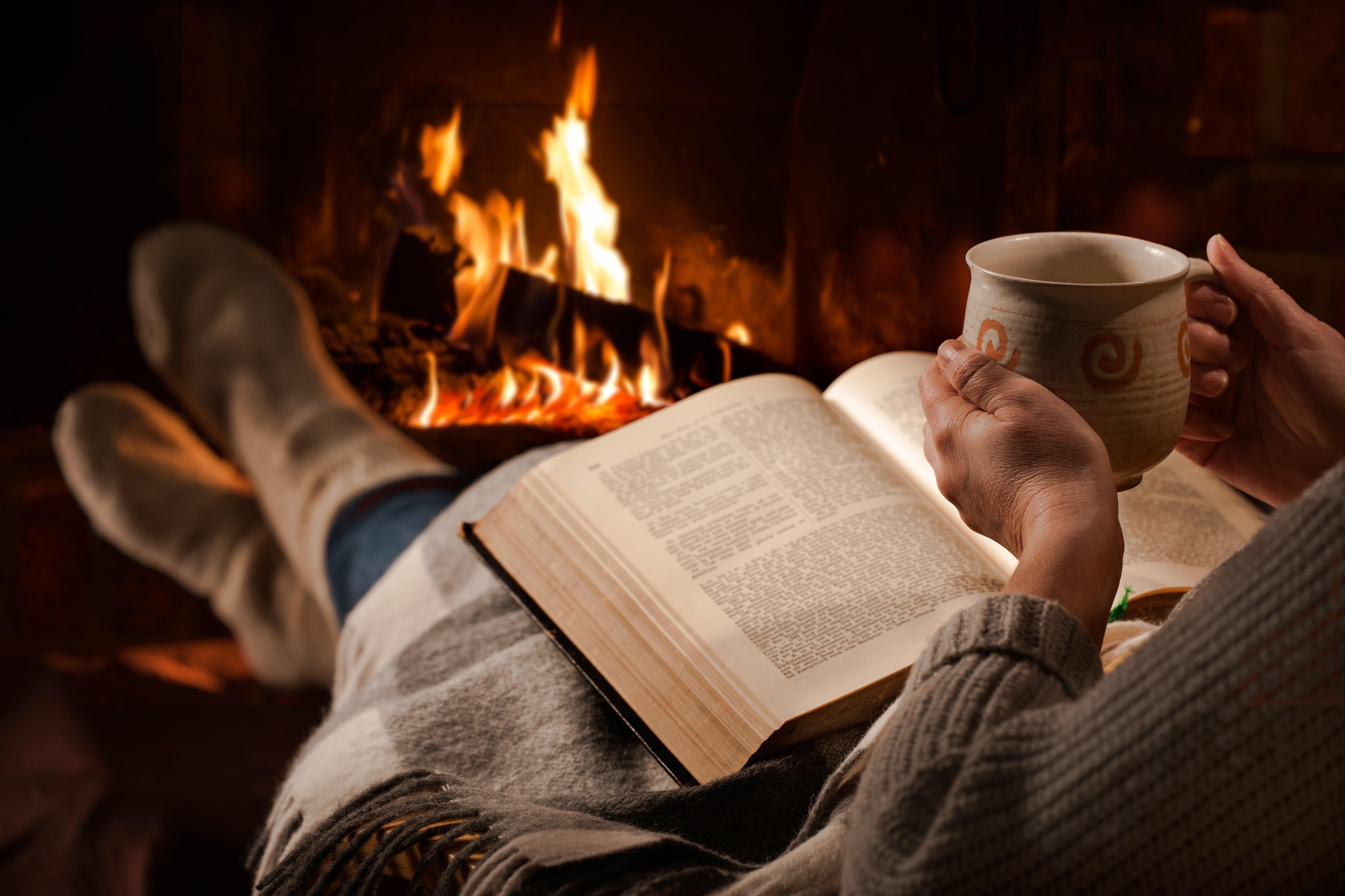 Personne qui a adopté le mode de vie hygge : devant son feu avec une boisson chaude et un bon livre